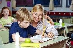 Estudante de ajuda do professor na sala de aula foto de stock royalty free