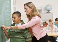 Estudante de ajuda do professor no quadro-negro Foto de Stock