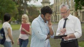 Estudante de explicação da misturado-raça das tarefas do professor de matemática perto da universidade, educação video estoque