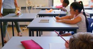 Estudante de explicação do professor fêmea na sala de aula na escola 4k filme