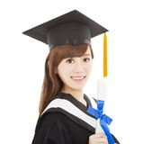 Estudante de graduado novo que guarda e que mostra o diploma imagens de stock royalty free