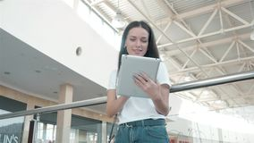 Estudante de jovem mulher bonito que usa sua tabuleta branca no shopping, vida feliz da universidade Fotos de Stock Royalty Free