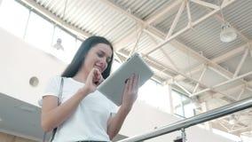 Estudante de jovem mulher bonito que usa sua tabuleta branca no shopping, vida feliz da universidade Imagens de Stock