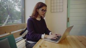 Estudante de jovem mulher com o portátil moderno que senta-se no café filme