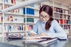 Estudante de jovem mulher que aprende na biblioteca Fotografia de Stock Royalty Free