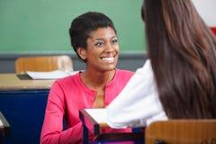 Estudante de Looking At Teenage do professor na mesa fotografia de stock