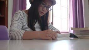 Estudante de mulher asiático que estuda na biblioteca filme
