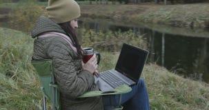 Estudante de mulher moreno novo que trabalha no portátil na natureza Dia bonito e mulher do outono que apreciam o ao usar o portá vídeos de arquivo