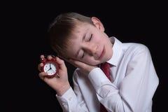 Estudante de sono com um despertador vermelho em suas m?os Conceito da manh? Fundo preto isolate imagem de stock
