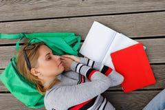Estudante de sono entre manuais de instruções no assoalho de madeira imagens de stock royalty free