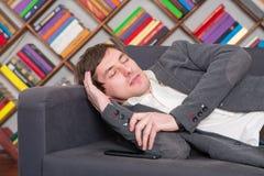Estudante de sono no sofá na biblioteca Imagem de Stock Royalty Free