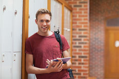 Estudante de sorriso considerável que inclina-se contra cacifos usando a tabuleta foto de stock royalty free