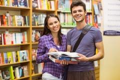 Estudante de sorriso dos amigos que guarda o livro de texto Foto de Stock Royalty Free