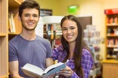 Estudante de sorriso dos amigos que guarda o livro de texto Imagens de Stock