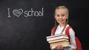 Estudante de sorriso que guarda livros, eu amo a escola escrita no quadro-negro, lição vídeos de arquivo