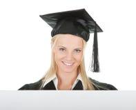 Estudante de terceiro ciclo fêmea que apresenta a placa vazia Fotografia de Stock Royalty Free