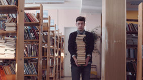 Estudante desconcertado com a pilha dos livros Fotografia de Stock Royalty Free