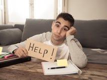 Estudante desesperado novo no esforço que trabalha e que estuda guardando um sinal da ajuda imagens de stock