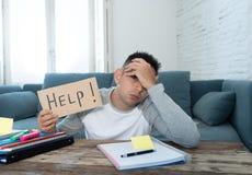 Estudante desesperado novo no esforço que trabalha e que estuda guardando um sinal da ajuda imagem de stock royalty free