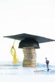 Estudante diminuto que está sobre 20 cédulas do Euro que olham o barrete em uma pilha de moedas Imagens de Stock