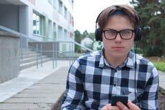 A estudante do adolescente do menino ou o estudante em uma camisa, sorrisos nos vidros, escutam a música no telefone imagem de stock