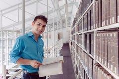 Estudante do homem novo que aprende lendo um livro na biblioteca Fotografia de Stock Royalty Free