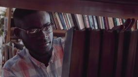 Estudante do homem novo que procura pelo livro na biblioteca Fotografia de Stock