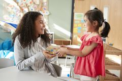 Estudante do jardim de infância que dá um presente a seu professor fêmea em uma sala de aula, vista lateral, fim acima fotos de stock royalty free