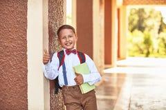 A estudante do menino que guarda um livro de texto que inclina-se contra a parede da escola mostra um sinal da mão da aprovação q fotos de stock