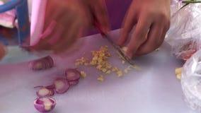 Estudante do principiante que desbasta a cebola e o alho durante a competição de cozimento anual vídeos de arquivo