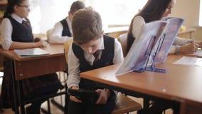 Estudante durante uma lição, jogando em um smartphone, escondendo do professor filme