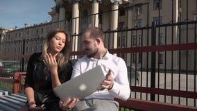 A estudante e o estudante companheiro comunicam-se em um banco no tempo ensolarado usando um portátil HD vídeos de arquivo