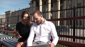 A estudante e o estudante do companheiro comunicam-se no banco no tempo ensolarado usando o portátil e o smartphone vídeos de arquivo
