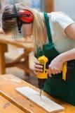 Estudante em uma classe da carpintaria que usa uma broca Fotografia de Stock Royalty Free
