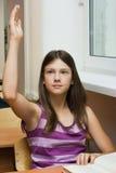 A estudante em uma lição levanta uma mão Imagens de Stock