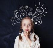 Estudante esperta da criança com pontos de interrogação da ampola e do giz imagem de stock