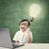 Estudante esperto do jardim de infância com lâmpada e portátil Fotografia de Stock