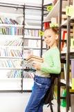 A estudante está e guarda livros na biblioteca imagens de stock