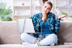 Estudante fêmea acorrentado com o portátil que senta-se no sofá Foto de Stock
