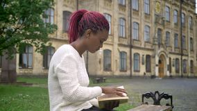 Estudante fêmea africano novo que senta-se no livro do banco e de leitura no parque perto da universidade, preparando-se para liç vídeos de arquivo