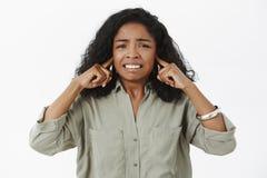 Estudante fêmea afro-americano irritado, desagradado incerto na camisa na moda que aperta os dentes que fecham as orelhas com índ imagens de stock