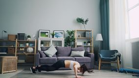 Estudante fêmea apto que exercita em casa fazendo flexões de braço e saltando o peso de perda filme