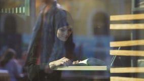 Estudante fêmea atrativo no livro de leitura árabe tradicional da roupa no café filme
