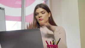 Estudante fêmea atrativo que força para fora, parecendo cansado ao trabalhar em um portátil video estoque