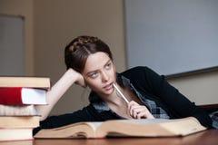 Estudante fêmea bonito em uma tabela com livros Fotografia de Stock Royalty Free