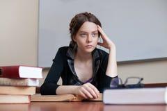Estudante fêmea bonito em uma tabela com livros Foto de Stock