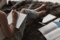 Estudante fêmea bonito novo Doing Homework na cama imagens de stock royalty free