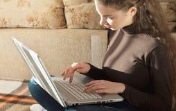 Estudante fêmea bonito novo Doing Homework na cama imagem de stock