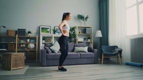 Estudante fêmea bonito que faz os esportes em casa que agacham-se apreciando o estilo de vida saudável vídeos de arquivo