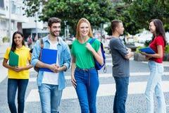 Estudante f?mea brit?nico e indiv?duo brasileiro com grupo de estudantes mutliethnic foto de stock royalty free
